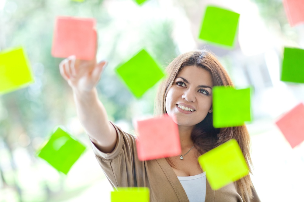 Multitask woman pointing at post-its and smiling